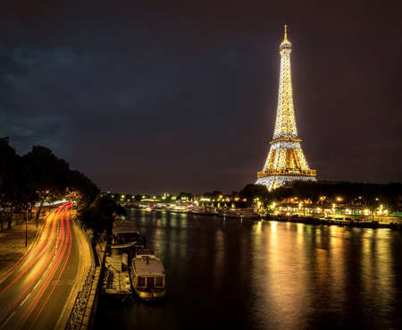 paris night: Eiffel Tower under motions clouds. Beautiful night view on one of famous popular place in Paris with long exposition.