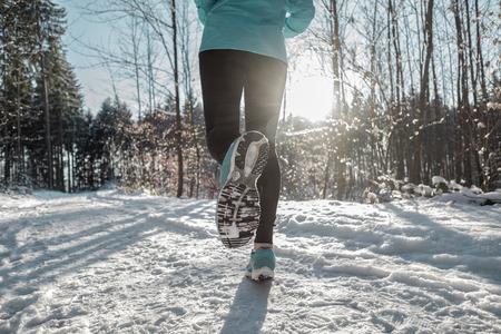 crosscountry: Woman Running at snowly winter under sunlight.