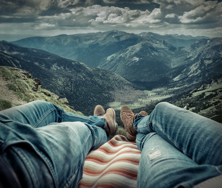 couple relaxing: Couple in car. Blonde female and male in jeans in them car looking on beautiful mountains view at autumn day.