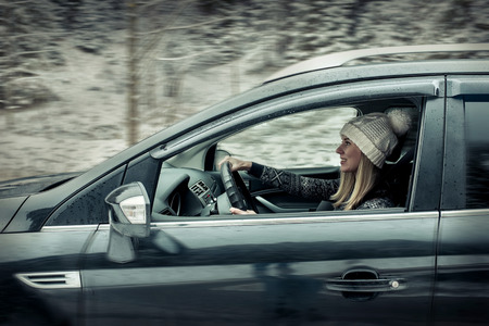 Woman at winter time. Yoyng female sitting and driving in black car at snowly winter day. Stockfoto