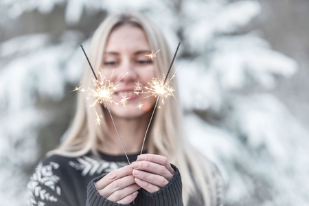 winter woman: woman with sparkler at winter.