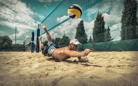 hitting: Beach volleyball player in action at sunny day under blue sky. Stock Photo