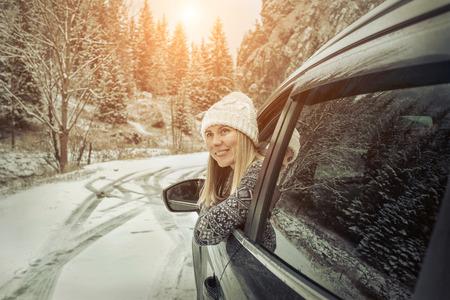 겨울 시간에 여자입니다. snowly 겨울 날에 그녀의 검은 자동차의 창에 찾고 Yoyng 여성.