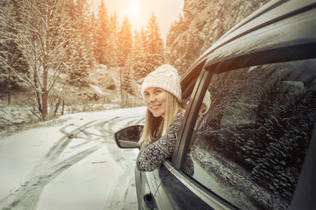 Vrouw in de winter. Yoyng vrouwelijke kijken in het venster van haar zwarte auto op snowly winterdag.