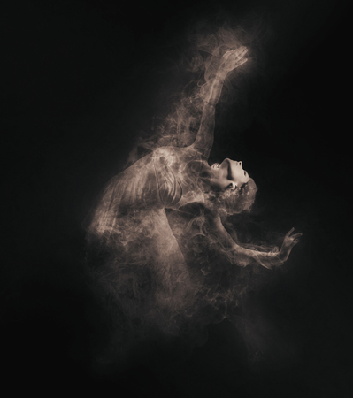 Dancer from smoke on the dark background photo