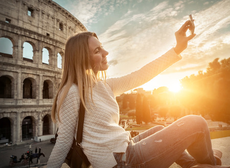 Woman tourist selfie with phone camera in hands near the Coliseum in Rome under sunlight and blue sky. Famous popular touristic place in the world.