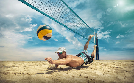 Beach volleyball player in action at sunny day under blue sky. Foto de archivo