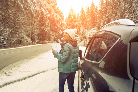 Woman at winter time. Yoyng female with touristic map in her hands sitting in black car at snowly winter day. Stock Photo