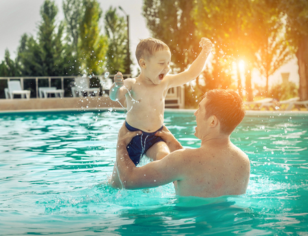 day light: Father and son funny in  water pool under sun light at summer day. Leisure and swimming at holidays.