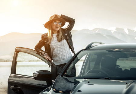 Woman at spreeng time. Yoyng happines female in hat and sunglasses stay near her black car at sunny day. Reklamní fotografie