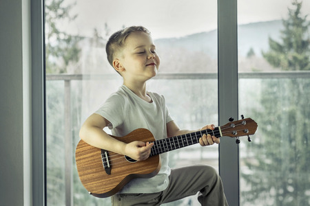 Young boy play on guitar at home at sunny day. Boy play on ukulele - hawaiian guitar. Banco de Imagens