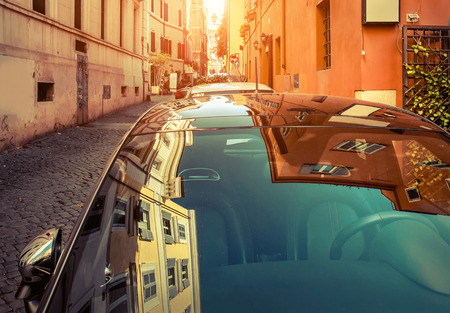 Car and his reflection on the glass on street in Rome - most popular historical travel place of the Italy and the world.