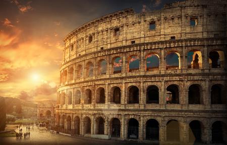 Roma, Italia. Uno de los lugares de viaje más populares en el mundo - Coliseo romano bajo la luz del sol de la tarde y el cielo de la salida del sol. Foto de archivo