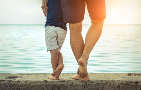 Father and son stay on the sea beach under sunlight at summer time. Close-up foots view on the sealine background at sunny day. Stock Photo