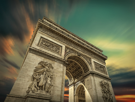 most popular: Arc de Triomphe in Paris under sky with clouds. One of symbols of France and one of the most popular tourist places in the world.