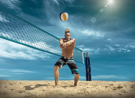 Beach volleyball player in action at sunny day under blue sky. Zdjęcie Seryjne