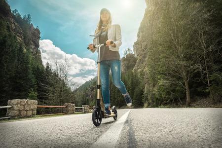 日当たりの良い夏の日に日光の下で、山の周りの道路の彼女のキック スクーターの女性。