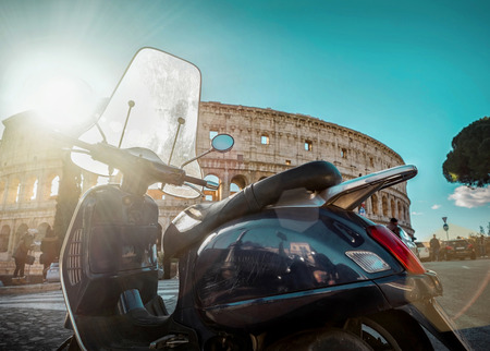 most popular: Retro scooter stay near the Roman Coliseum under blue sky with sun light at day time. Scooters and Coliseum are the symbols of Rome - most popular historical travel place of the Italy and in the world. Editorial