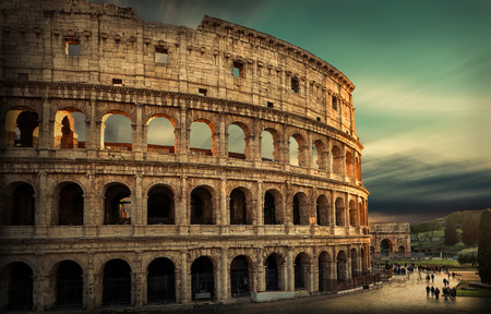 Roman Coliseum under evening sun light and sunrise sky. Stock Photo
