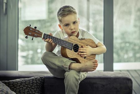 Young boy play on guitar at home at sunny day. Boy play on ukulele - hawaiian guitar. photo