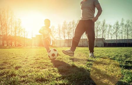 Vader en zoon spelen samen met bal in voetbal onder zonlicht. Groen veld in het stadspark op zonnige dag.