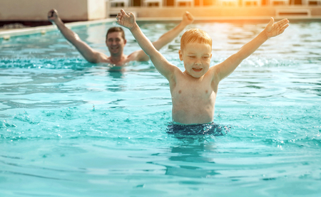 Father and son funny in  water pool under sun light at summer day. Leisure and swimming at holidays. photo