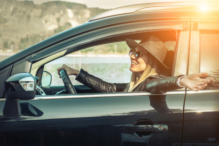 Woman at spreeng time. Yoyng happines female in hat and sunglasses sitting in her black car at sunny day. photo