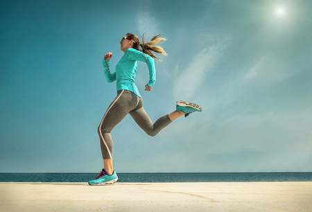 Woman running along the sealine coast under sunlight at sunny summer day. photo