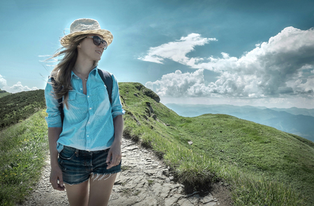 Woman hiking in mountains at sunny day time. photo