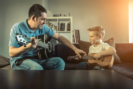 Father teaching his son to play on guitar at home. Son play on ukulele - hawaiian guitar. photo