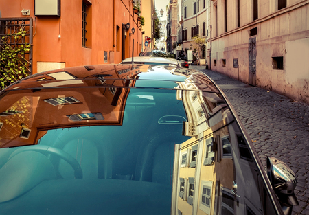 Car and his reflection on the glass on street in Rome - most popular historical travel place of the Italy and the world. Banco de Imagens - 87903493