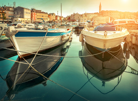 The white boats stay near the pier in port on the sealine under sunlight at summer day. Travel place Rovinj  in Croatia. Stock Photo