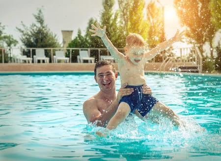 Père et fils drôle dans la piscine sous la lumière du soleil en été. Loisirs et baignade en vacances. Banque d'images - 85158234