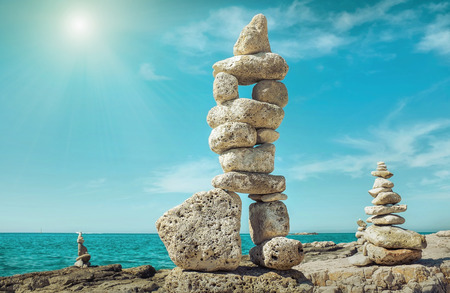 Composition of stones on the seacost under blue sku with clouds on sunny day. Stok Fotoğraf