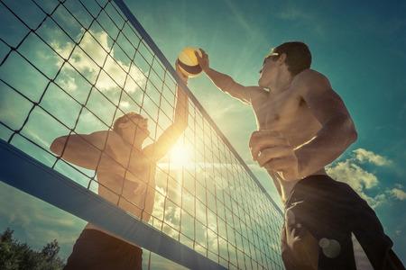Beachvolleyballspieler in der Sonnenbrille unter Sonnenlicht. Dynamische Sportaktion im Freien. Standard-Bild
