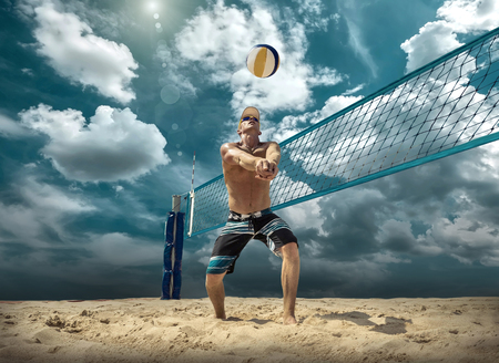 Beach volleyball player in action at sunny day under blue sky. Imagens
