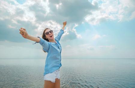 幸せな女に宿泊し、日当たりの良い夏の日に日光の下で海のビーチでリラックスします。
