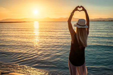 Blonde woman in summer hat stay on the coastline by the sea beach with heart symbol of her hands. Sea sunset view. Freedom. Wind. Summer. Beach. Sunset. Vacation. Looking to a sky and sea. Looking forward.
