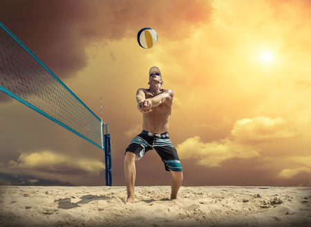 net: Beach volleyball player in action at sunny day under blue sky. Stock Photo