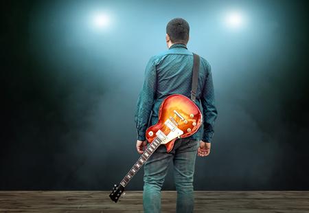 Kunstenaar Gitarist handen spelen op elektriciteit gitaar onder licht, oefenen in spelen. Liedentertainment en muziekinstrument.