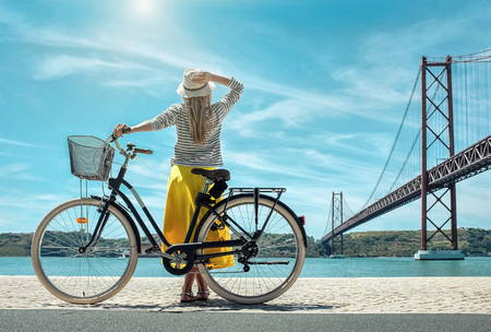 Blonde woman in summer hat and yellow skirt with her city bicycle walking coastline near the bridge under sunlight in sunny summer day. Foto de archivo - 89100435