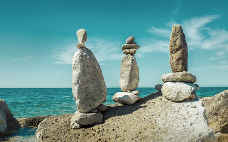 Composition of stones on the seacost under blue sku with clouds on sunny day. Banco de Imagens