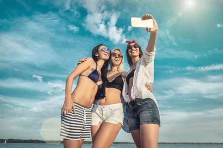 Three young pretty women in sunglasses having fun on the beach and doing selfie with them camera phone under sunlight in sunny day.