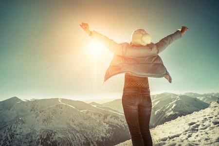 Mujer feliz que se relaja en la cima de la montaña debajo del cielo azul con luz del sol en el día de invierno soleado, vacaciones del viaje, fondo de las montañas del paisaje.