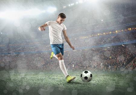 Jogador de futebol em um campo de futebol em ação dinâmica no dia de verão sob o céu com nuvens. O homem desportivo está atirando a bola ao ar livre. Foto de archivo