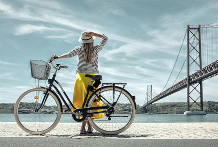 Blonde woman in summer hat and yellow skirt with her city bicycle walking coastline near the bridge under sunlight in sunny summer day.