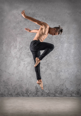 Man dancer, in beautiful dynamic jump action figure on the grunge background. Stock Photo