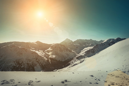 Nice mountains view at sunny day with skiers under blue sky with sun light at winter time. Stock Photo - 92601439