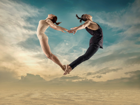 Two person, dancers, woman and man in dynamic jump action  heart figure under sunlight in sunny day under blue sky. Imagens