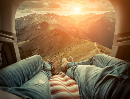 Couple in car. Blonde female and male in jeans in them car looking on beautiful mountains view at autumn day.